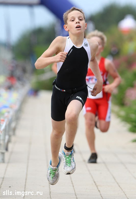 young boy in black lycra sport clothes running hard during a triathlon athletism competition