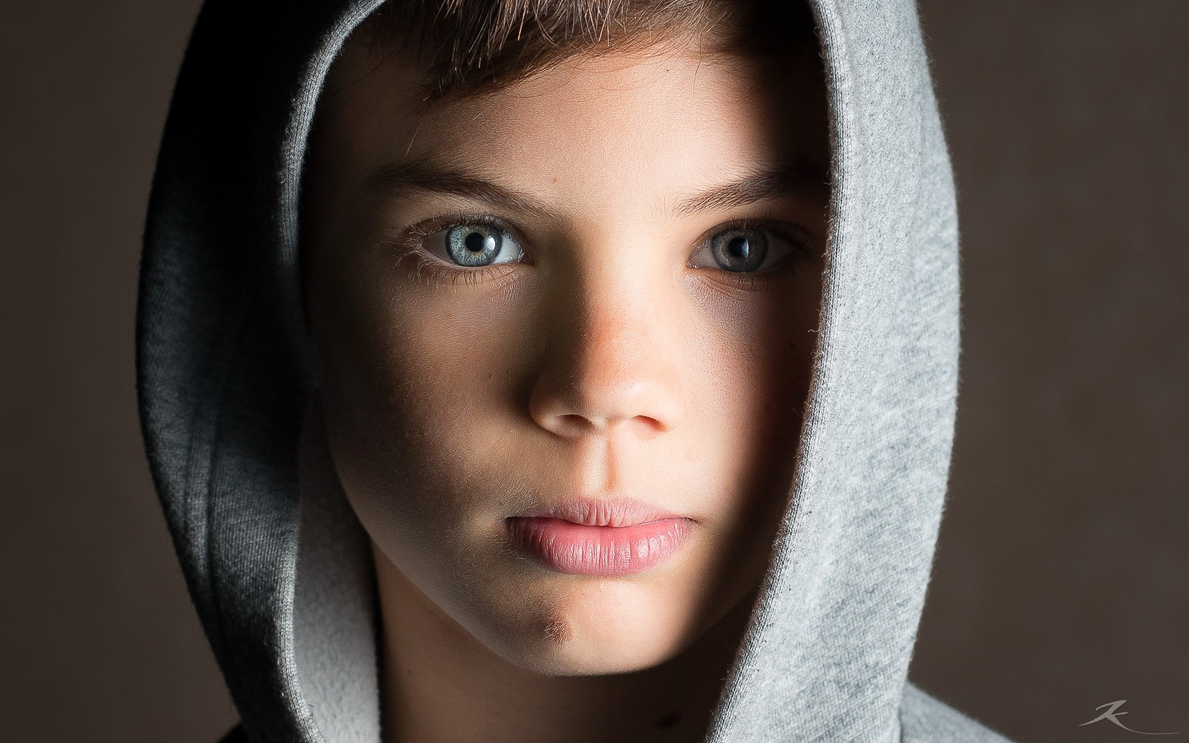 young boy with grey hoodie and deep blue eyes