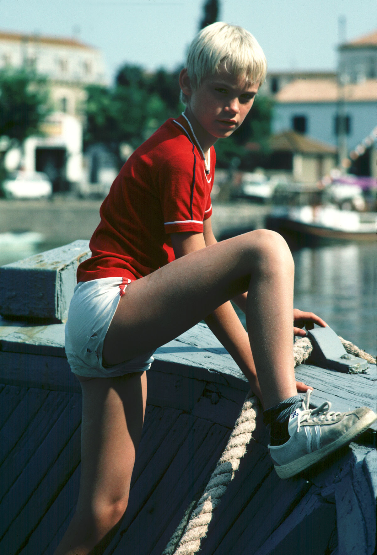 vintage young blonde boy in white shorts and red tee shirt on a boat