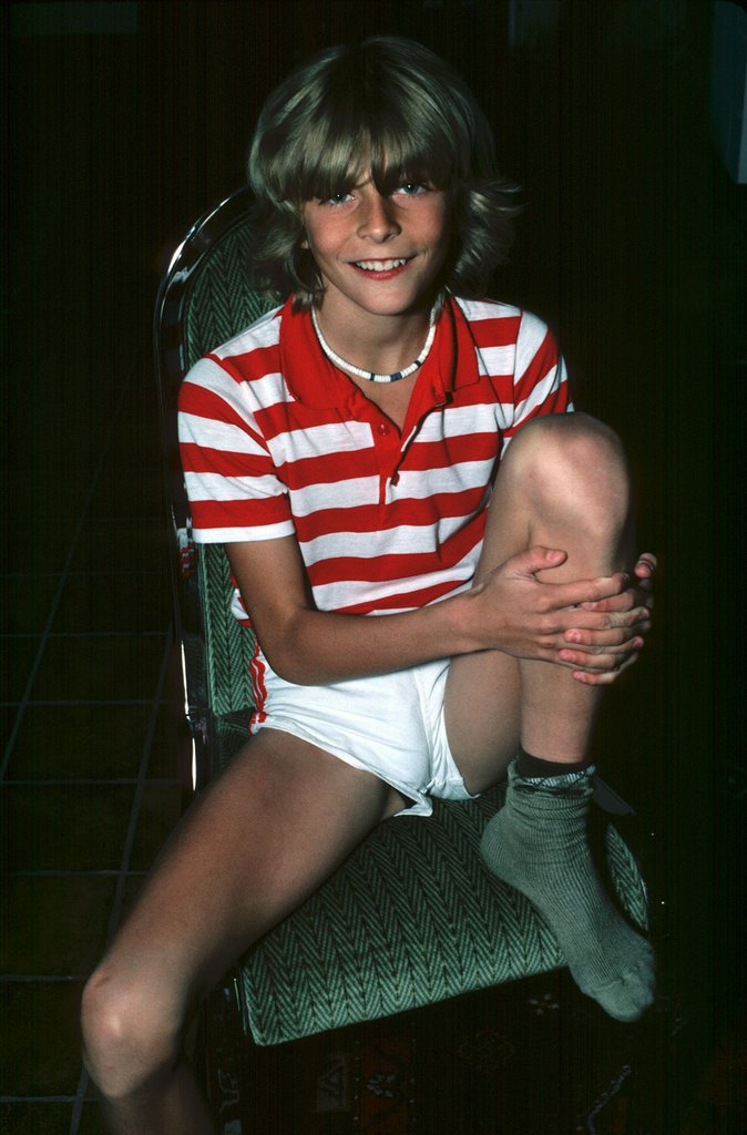 vintage picture of a young boy in white shorts wearing a red and white shirt with socks