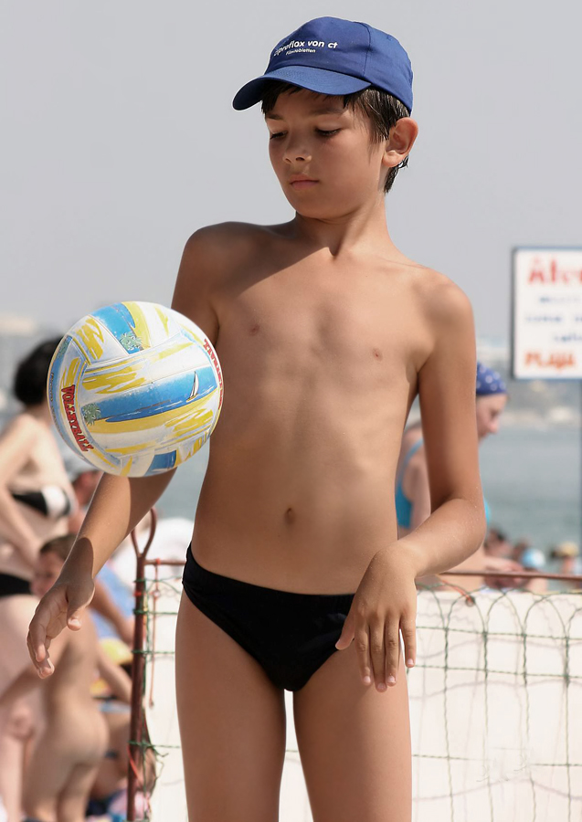 young boy in black speedo swimsuit wearing a blue hat and playing with a ball at the beach