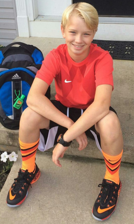 young blonde boy in sneakers and orange socks wearing a nike shirt