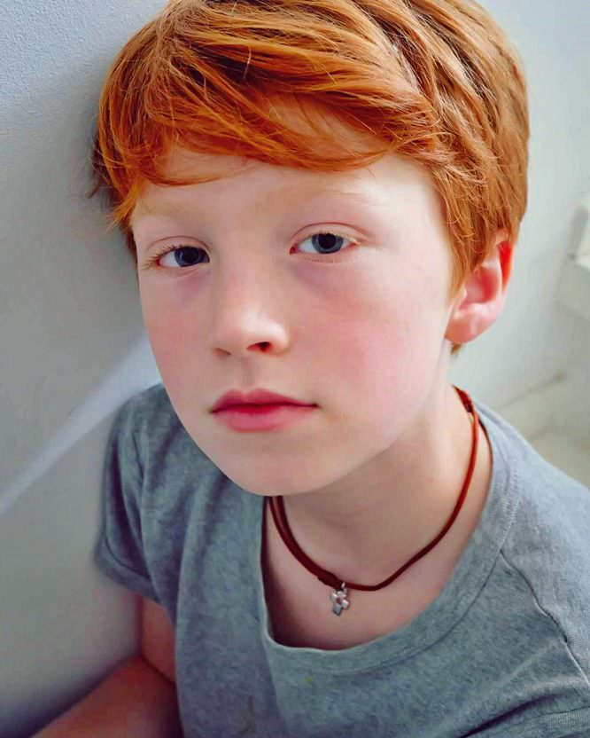 redhead ginger boy wearing a grey shirt and a red necklace