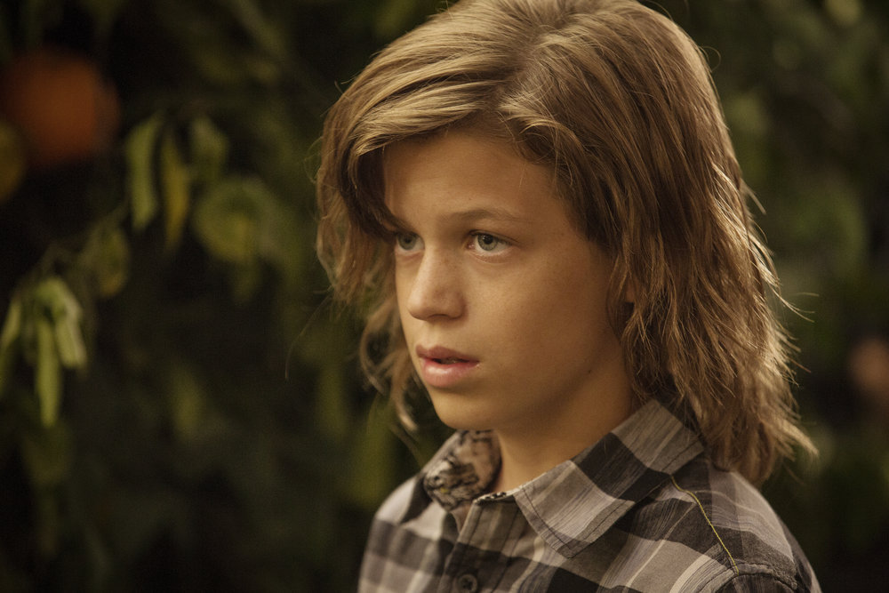 boy actor jacob buster with a squared shirt and long hair