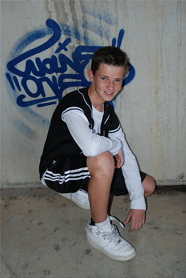 young boy in shorts smiling at the camera