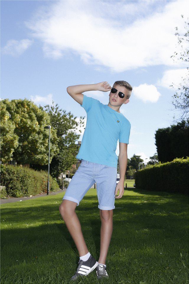 young blonde boy in blue shirt, shorts with sunglasses