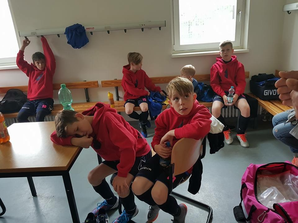 many young boys in a classroom after a soccer game