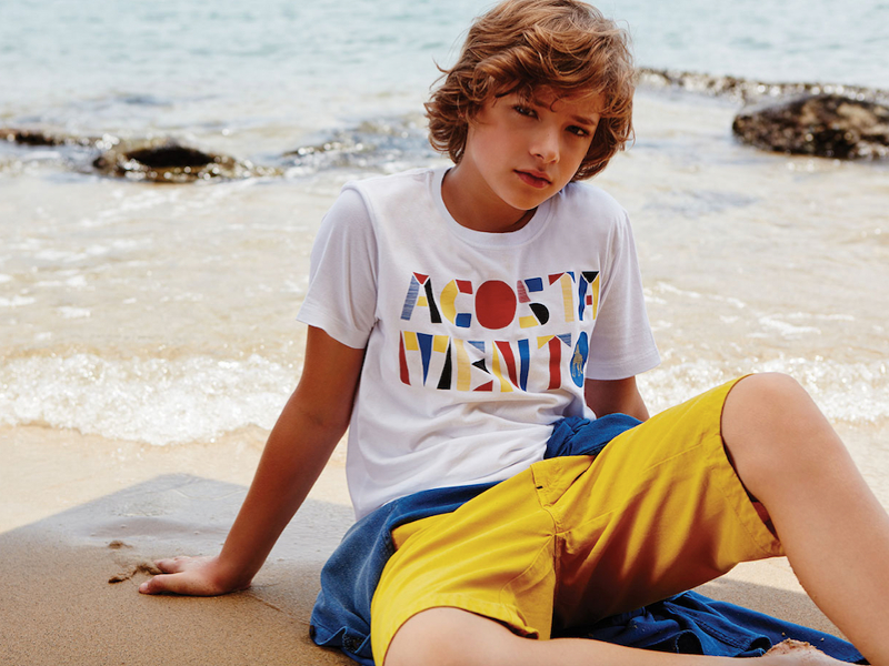 young boy in yellow shorts on the beach