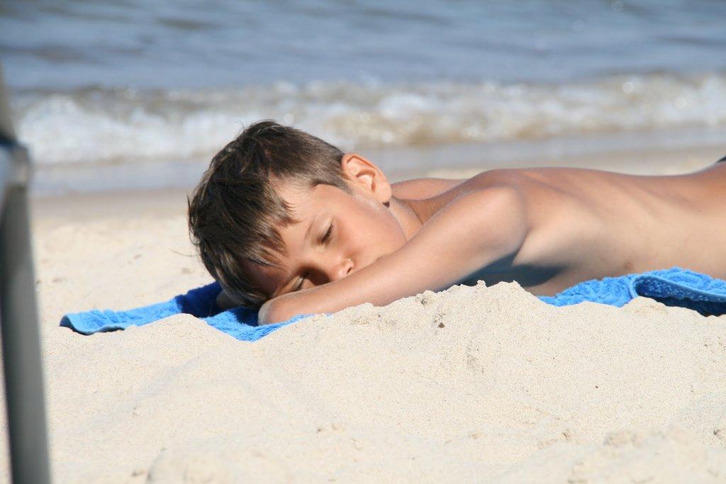 boy sleeping on the beach